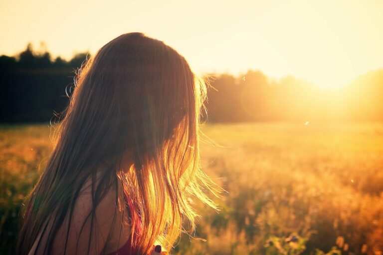 Ung pige står på marken og ser på solopgang. Kroppen husker mobning