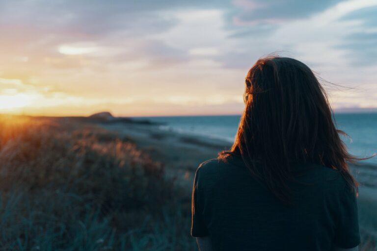 Kvinde kigger på solnedgang og tænker over livet. Livskriser