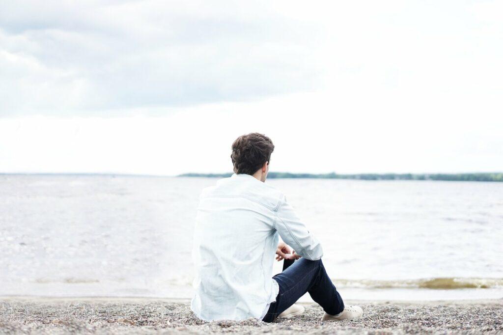 Bekymret mand sider på stranden